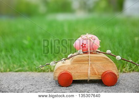 Decorative toy car with pussy willow and Easter egg on green grass background
