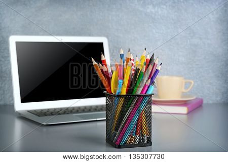 Pencils and pens in metal holder with laptop  on grey table