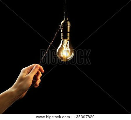 Female hand turning on light bulb on black background, close up
