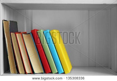 Many books on wooden shelf