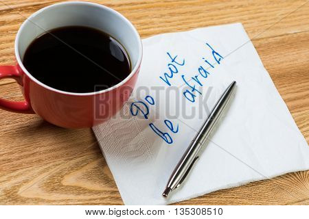 Coffee cup pen and napkin with words on paper note