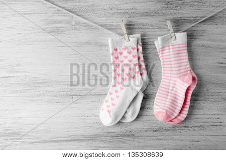 Baby socks hanging on the clothesline on wooden background