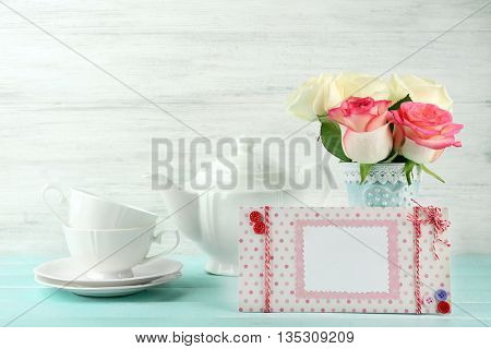 Beautiful bouquet of roses and handmade postcard on light wooden background