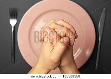 Female hands and empty plate on dark background