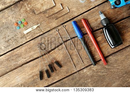 Tattoo supplies on wooden background