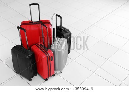 Different suitcases on tile floor, close up