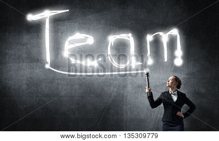 Young elegant businesswoman with flashlight draw word team