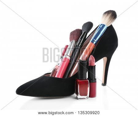 Makeup set with black woman's shoe, brushes and cosmetics, isolated on white