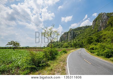 Two lane road surrounded with limestone mountain and forest in Thailand. Suitable for use as wallpapers.