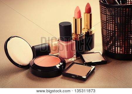 Decorative cosmetics and accessories for makeup on beige background