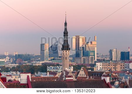 Aerial cityscape with old town hall spire and modern office buildings skyscrapers in the background in the evening, Tallinn, Estonia