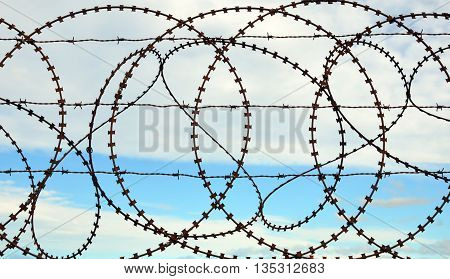 Patterns in a barbed wire fence with sky background