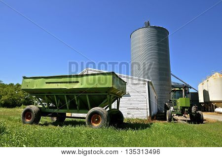 An old gravity grain box, tractor, wood granary, grain bins, and augers for harvest