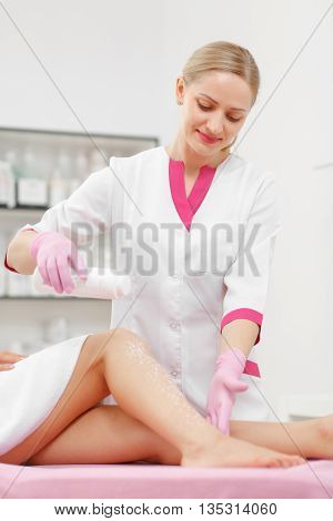 Woman beautician prepares the skin for legs Hair removal. Sugaring: Beauty Concept. Skin Care. Hair removal Procedure. Cosmetology. Cosmetology salon