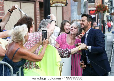 NASHVILLE, TN-SEP 1: Luke Bryan takes selfies with the crowd at the 9th Annual ACM Honors at the Ryman Auditorium on September 1, 2015 in Nashville, Tennessee.