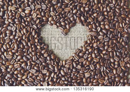 Burlap texture heart shape with coffee beans background. Sack cloth burlap texture, love coffee. Natural sackcloth canvas background with heart frame and copy space. Coffee border at hessian textile