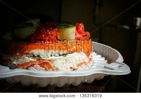 Salmon Sushi Cake with nigiri, soy sauce, cucumber, salmon, avocado, caviar, nori sesame Side view