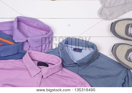 Set Of Men's Clothing And Shoes On Wooden Background. Sports T-shirt And Sneakers In Bright Colors.