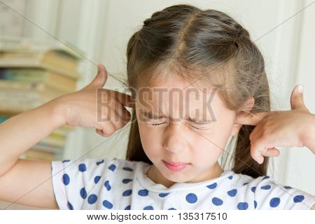Little girl covering her ears. Negative emotion