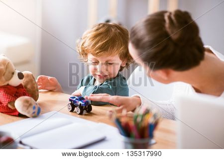 Lets play. Young mother playing with her little smiling child while sitting at the table