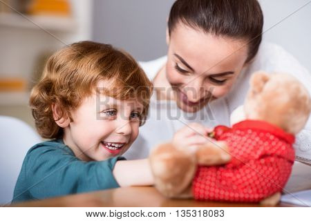 You are my friend. Joyful little cute boy playing with a teddy bear while sitting at the table with her mother