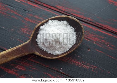 white crystals sea salt on wooden spoon on black old background