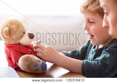 Look at it. Amused little cute child dressing his teddy bear while sitting at the table with his young mother