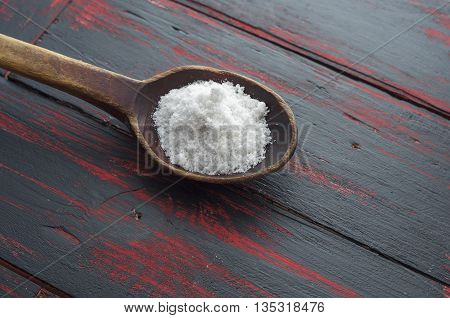 white coarse salt in a wooden spoon