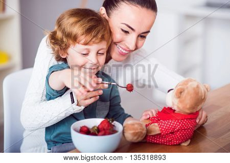 Open your mouth. Young delighted mother and her cute little son feeding strawberry to the teddy bear while sitting at the table