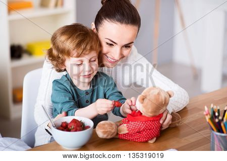 I like playing with my teddy. Young cheerful mother and her funny little son feeding strawberry to the teddy bear while sitting at the table