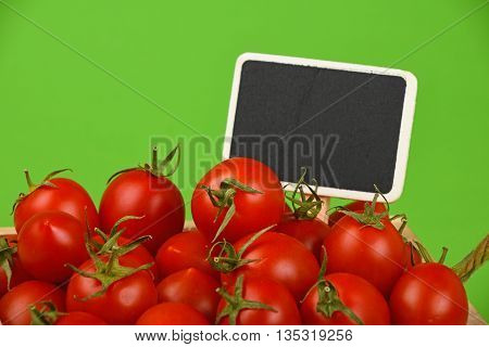 Red Tomatoes With Price Sign Over Green