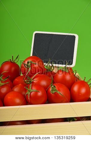 Red Tomatoes In Box With Price Sign Over Green