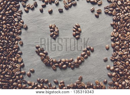 Smiley face from coffee beans. Heap of roasted coffee bean on grey stone surface texture. Coffee shop or cafe background. Natural stone and smiling face from beans. Soft color toning, top view