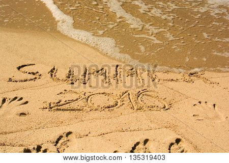 inscription on wet sand summer 2016 with footprints. Concept photo the end of summer vacation