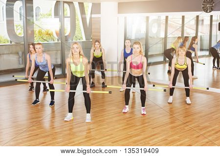 Group of young women in fitness class. Group of people making exercises. Girls do squats with barbells. Healthy lifestyle, training, sport, gym studio. Girls in fitness club, squats with weights.