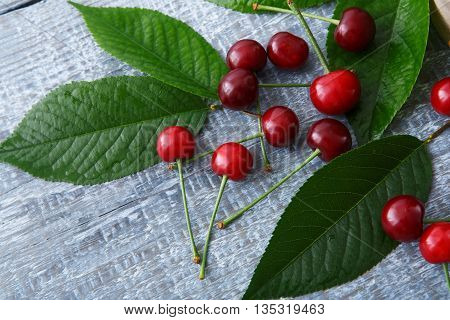 Sweet fresh cherries with green leaves on blue rustic wood. Cherry fruit backround. Garden fresh organic cherries at wooden table closeup, top view. Food background.