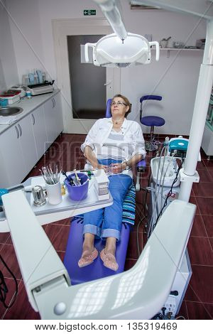 beautiful mature woman in the dentist's chair waiting for a dental examination