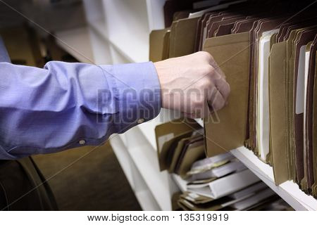 Businessman reaching for files on shelf for information storage