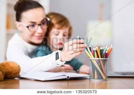 We need green. Picture of a woman choosing a crayon in a pencil cup while sitting at the table with her son