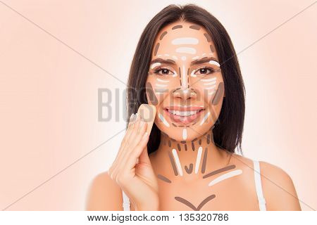 Close-up Photo Of Pretty Smiling Woman With Sponge Doing Professional Contouring Face Make-up Sample