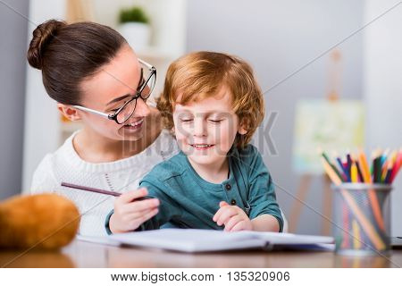Like this. Young woman with glasses smiling and looking at her son drawing with color pencils
