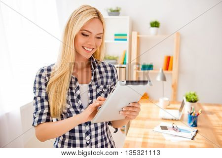 Portrait Of Happy Young Blonde Using Digital Tablet In Office