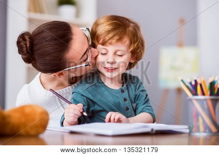 My precious. Young woman with glasses kissing her son while he drawing and sitting at the table