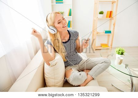 Happy Girl Sitting On Sofa, Listening Music And Dancing