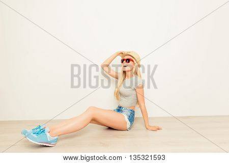 Young Girl In Hat And Glasses Sitting On Floor And Looking Way