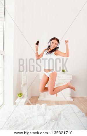 Happy Music Lover In Headphones Jumping On Bed And Listening Music