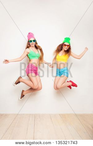 Pretty  Girls In Hats And Glasses Having Fun And Jumping