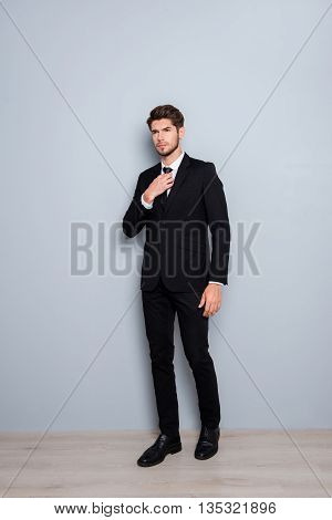 Full Length Portrait Of Young Businessman In Black Suit Correcting Tie
