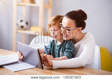 Click on it. Young delighted woman with glasses and her son using a tablet while sitting with him at the table