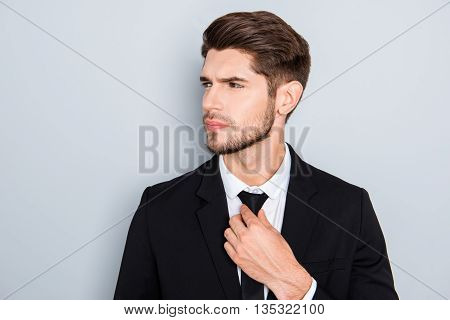 Portrait Of Confident Young Man Correcting His Tie